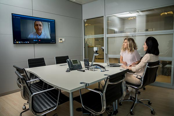Several Nielsen employees collaborating on a project in the office in Cyprus along with a teammate from a remote location on video chat