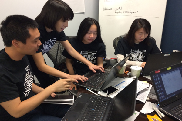 Several young people working hard at a hackathon