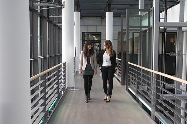 An exterior view of Nielsen's office in Germany with employees walking and discussing