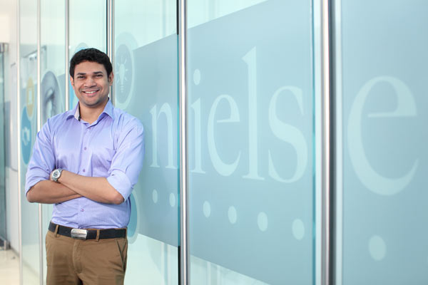Nielsen employee posing in front of the logo in the Nielsen office in Gurgaon