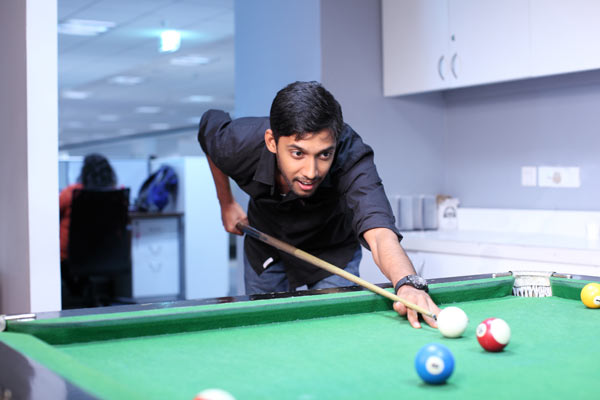 Nielsen employee playing billiards in breakroom of the Nielsen Gurgaon office.