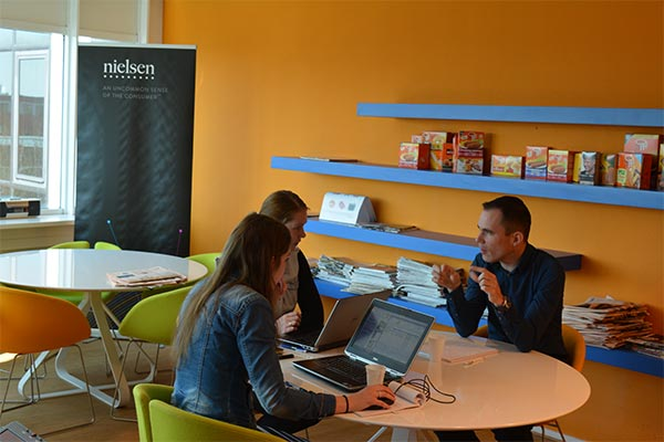3 employees communicating in Nielsen Netherlands office