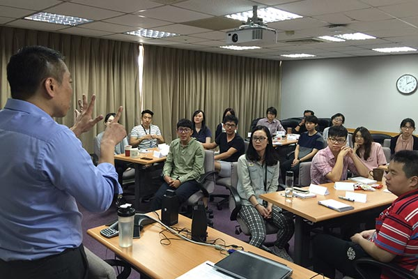 A group of Nielsen employees listening to a presentation in the Taiwan office
