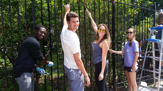 Nielsen volunteers painting gate