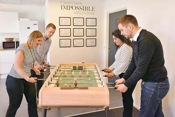 Several Nielsen employees playing foosball in the Denmark office