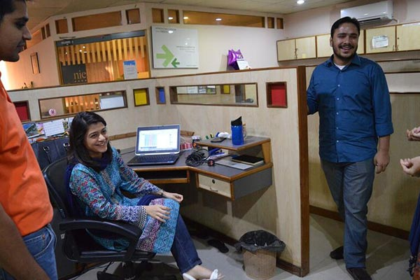 Employees collaborating in the Nielsen office in Pakistan