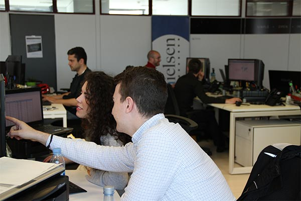 An interior view of the Nielsen office in Spain with employees collaborating on their project