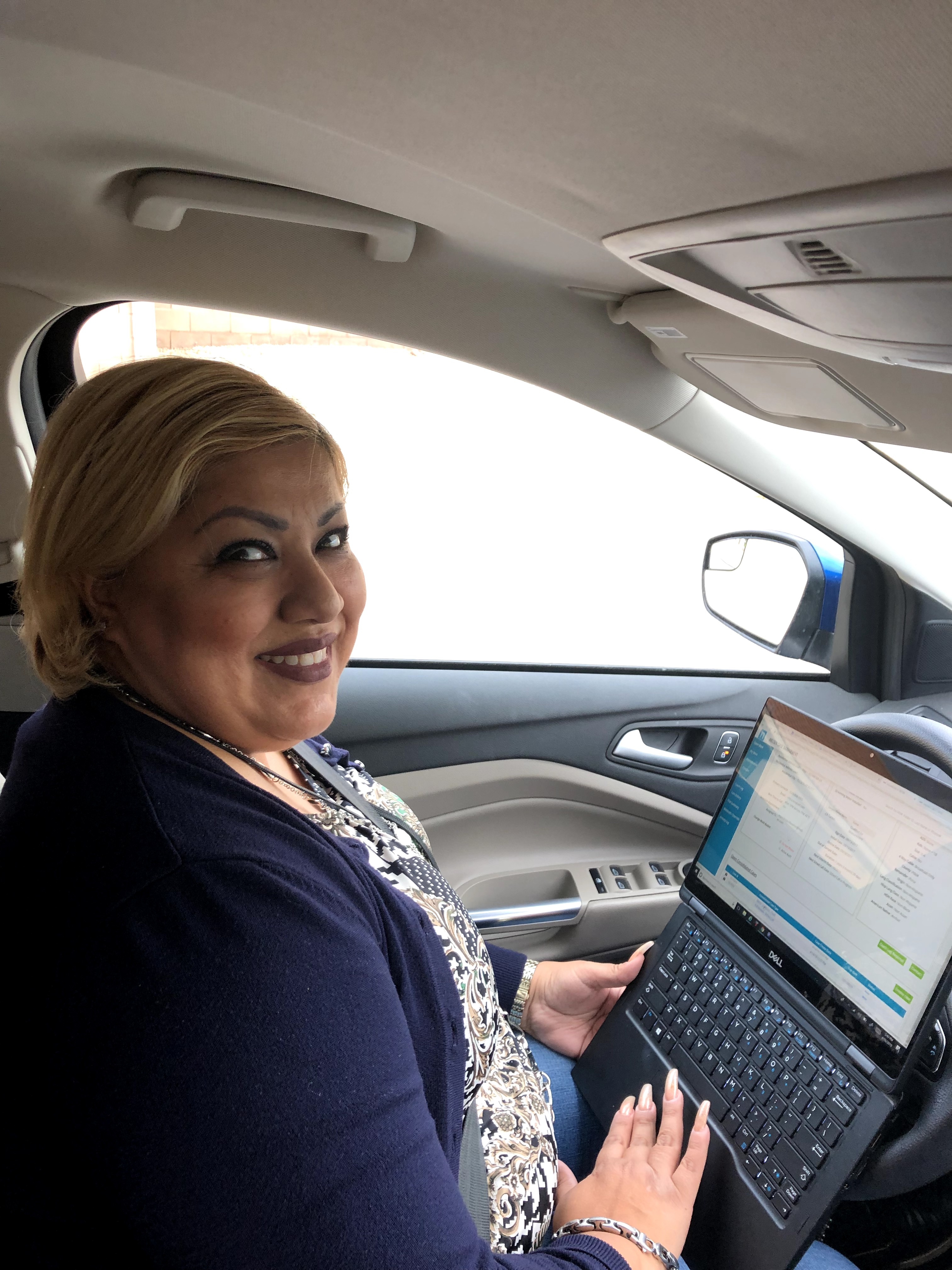 Nielsen Representative with a laptop in her car